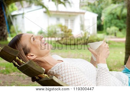 Happy Woman Lying Down In Hammock With Cup Of Coffee
