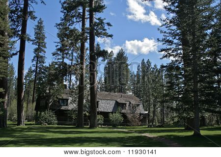 Beautiful mountain lake-front vintage cottage with grass and trees.