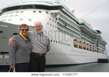 Senior couple ready for another cruise in front of a cruise ship.