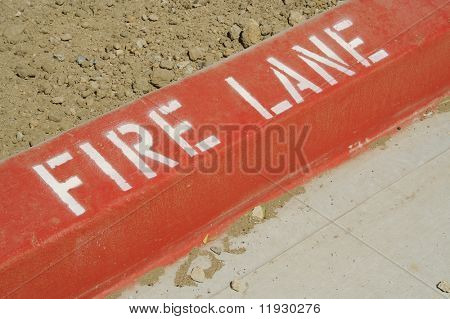 Close-up of red painted curb with Fire Lane text.