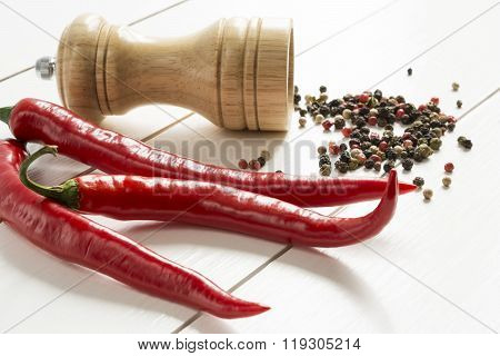 Red Pepper And Pepper Mill Peppercorns Scattered On A White Wooden Table