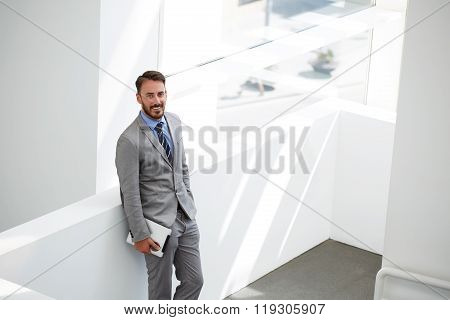 Smiling businessman standing with digital tablet in office interior