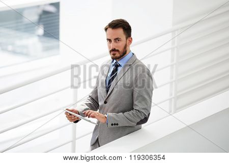 Half length portrait of rich businessman holding portable digital tablet during work break