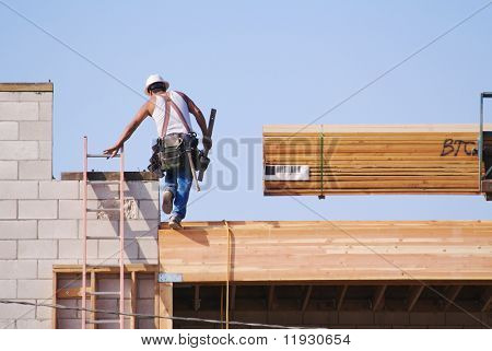 Carpenter climbing up ladder at a construction scene.