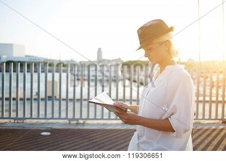 Charming female tourist reading location map while standing on bridge near sea in sunny summer day
