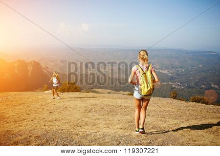 Back view of young woman standing on a mountain hill and waiting her friend which standing below