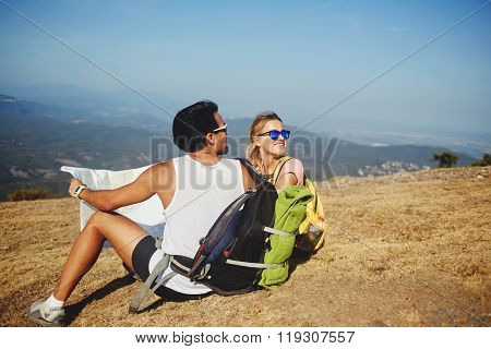 Young man and woman wanderers enjoying beautiful landscape during summer hike overseas