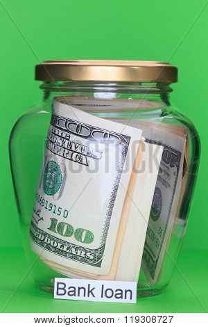 Money In Glass Jars, On Green Background With Sign – Bank Loan