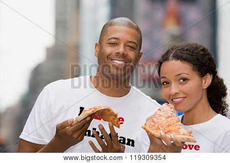 Couple holding pizza
