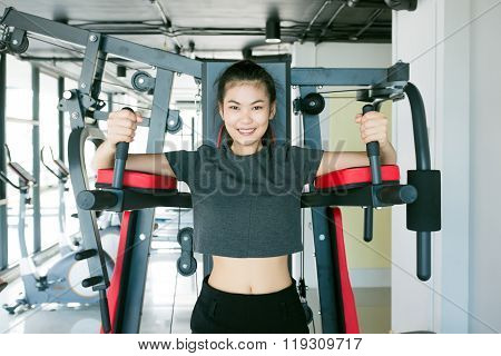 Asian Woman Exercising On Shoulder Press Machine
