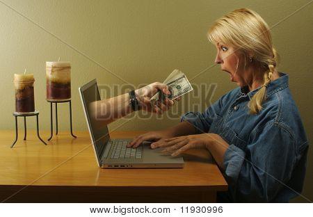 Mujer de negocios atractivo se sorprendió al ver una mano que viene a través de su pantalla de ordenador portátil entrega sus lotes de