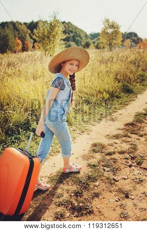 happy child girl with suitcase travelling on summer vacation. Kid going to countryside.