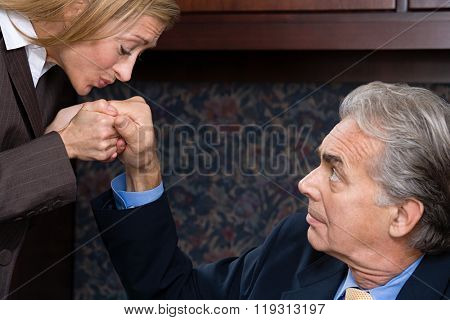 Woman kissing businessman's hand