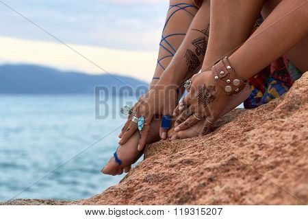 girls hands with feet, mehendi,accessories, on mountain sea