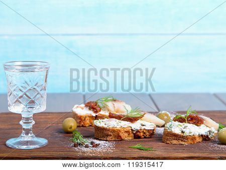 Herring sandwich with sun-dried tomatoes herbs basil soft cream cheese and a shot of vodka.