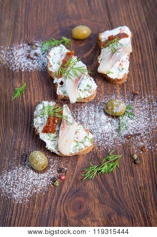 Herring sandwich with sun-dried tomatoes herbs basil and soft cream cheese.