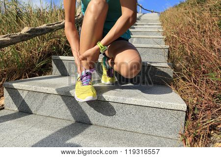 young woman trail runner hold her sports injured ankle