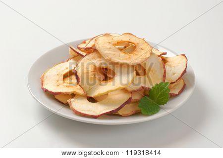 plate of dried apple chips on white background - close up