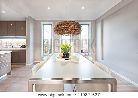 Interior Of A Modern Dining Room With A Long White Table And Bamboo Or Rattan Lamp