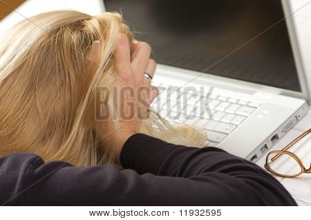 Female hold her head in frustration  while using her laptop.