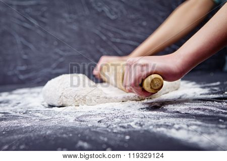 Girl rolls out the pizza dough with the rolling pin on black table