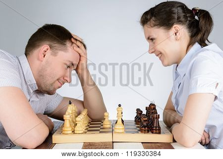 Woman Laughing While Playing Chess Against A Brooding Man