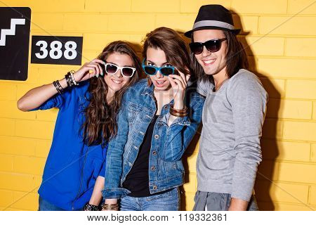 Happy Young People Having Fun In Front Of Yellow Brick Wall