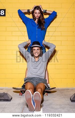 Happy Young Couple Having Fun In Front Of Yellow Brick Wall