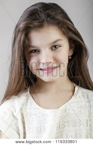 Portrait of a charming brunette little girl, isolated on gray background