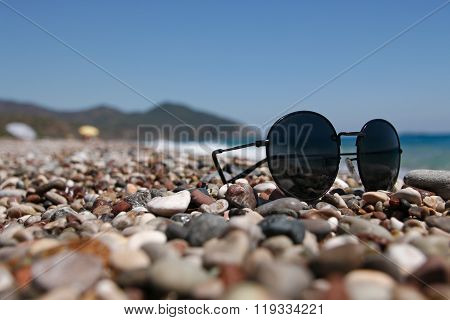 Sunglasses On A Pebble Beach By The Sea.
