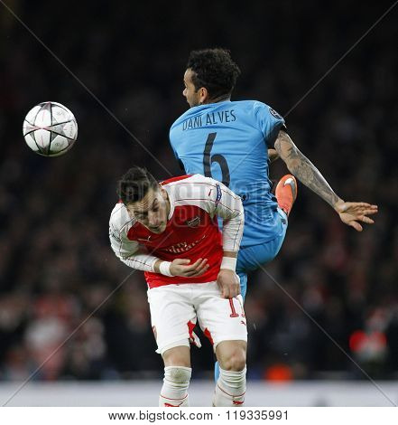 LONDON, ENGLAND - FEBRUARY 23: Mesut Ozil of Arsenal and Daniel Alves of Barcelona compete for the ball during the Champions League match between Arsenal and Barcelona at The Emirates Stadium