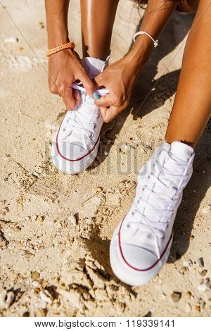 Beautiful Teenage Black Girl In White Sneakers On The Sand Of Beach.