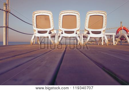 Deckchairs On A Pier Overlooking The Sea Sunset