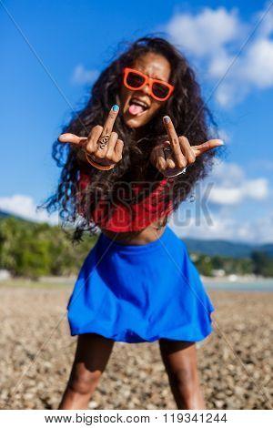 Beautiful Teenage Black Girl In Blue Skirt And Pink Bra On The Rock Beach.