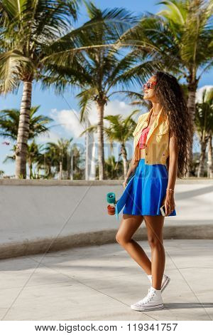 Beautiful Teenage Black Girl In Blue Skirt Stand With Her Smartphone.