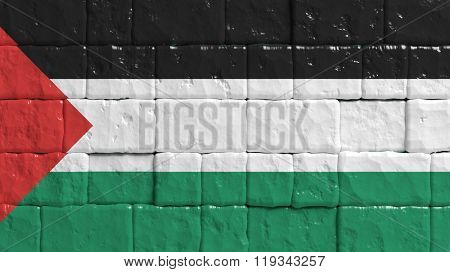 Brick wall with painted flag of Palestine