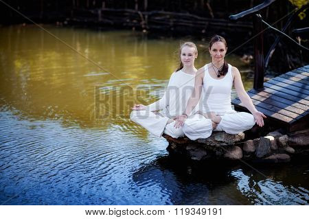 Outdoor yoga session in beautiful place by a lake - meditation