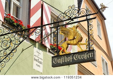 ROTHENBURG OB DER TAUBER GERMANY - AUGUST 10 2015: A wrought iron hanging sign in Rothenburg one of the best-preserved medieval towns in Europe part of the famous Romantic Road tourist route