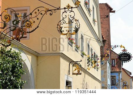 ROTHENBURG OB DER TAUBER GERMANY - AUGUST 10 2015: Traditional wrought iron hanging signs in one of the best-preserved medieval towns in Europe part of the famous Romantic Road tourist route.