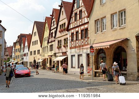 ROTHENBURG OB DER TAUBER GERMANY - AUGUST 10 2015: Rodergasse street in Rothenburg one of the best-preserved medieval towns in Europe part of the famous Romantic Road tourist route.