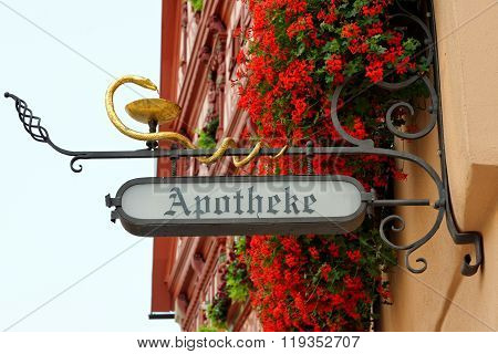 DINKELSBUHL GERMANY - AUGUST 10 2015: A drugstore wrought iron hanging sign in Dinkelsbuhl one of the best-preserved medieval towns in Europe part of the famous Romantic Road tourist route