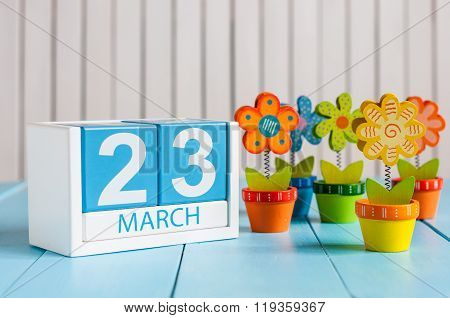 March 23rd. Cube calendar for march 23 on wooden surface with colour flower. Spring concept