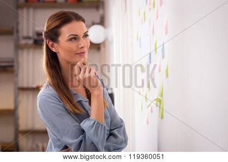 Happy woman looking a sticky notes on wall. Concentrated woman artist looking at colorful sticky notes at the office. Young designer looking up at sticky notes on wallin creative office.