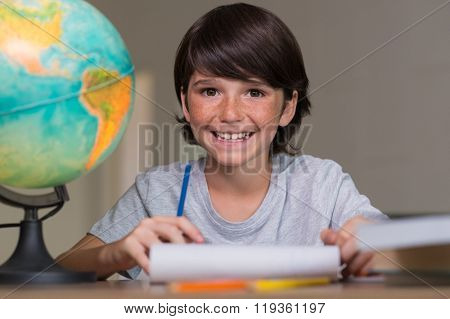 Closeup of little boy doing homework beside globe of earth. Portrait of happy young boy smiling and looking at camera sitting at desk. Cheerful cute boy doing his homework at desk.