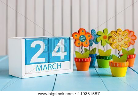 March 24th. Cube calendar for march 24 on wooden surface with colour flower. Spring concept