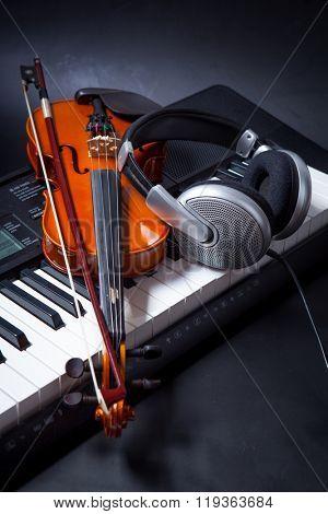 Violin, piano keys and headphones on black