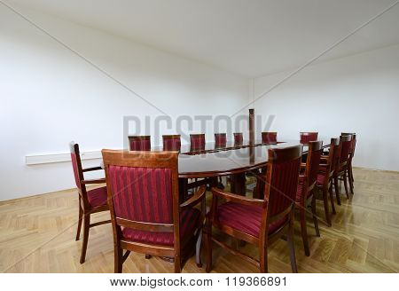 Conference room, big wooden table and marron chairs