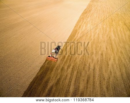 Aerial view of ploughed field with tractor. Industrial background on agricultural theme.