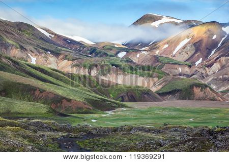 Snow and fog lies in the hollows of colorful rhyolite mountains.  Summer morning in the National Park Landmannalaugar, Iceland. Green Valley is flooded with melt water