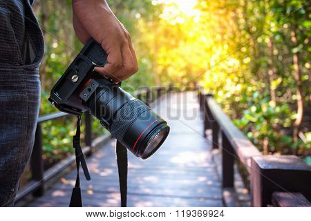 Man holding his camera on walkway during his travel